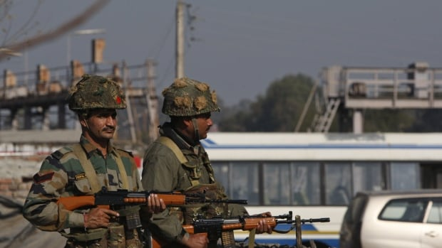 Indian army soldiers take positions outside the Indian airbase in Pathankot, 430 kilometres north of New Delhi, India, on Saturday, Jan. 2, 2016. At least four gunmen entered an Indian air force base near the border with Pakistan on Saturday morning and exchanged fire with security forces, leaving two of them dead, officials said.