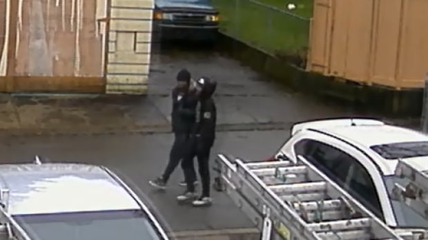 Two men seen walking in this image are alleged suspects in a Surrey home invasion attempt, caught on surveillance video tape, according to Surrey RCMP.
