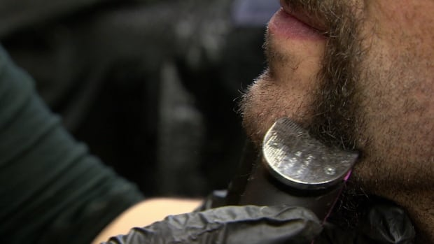 Michael Shaw has the remaining bits of his beard shaved off at Tommy Gun's Original Barbershop in Saskatoon for a fundraising event.