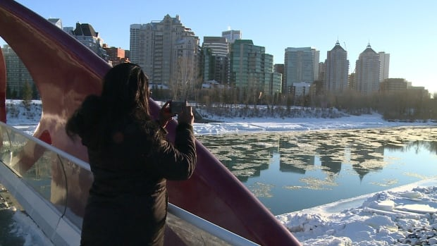 A woman takes a photograph from Calgary Peace Bridge