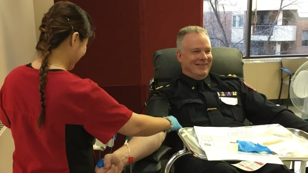 "Calgary Police Chief Roger Chaffin donates blood for the first time. ""I didn't cry or anything yet, so it should be fine."""