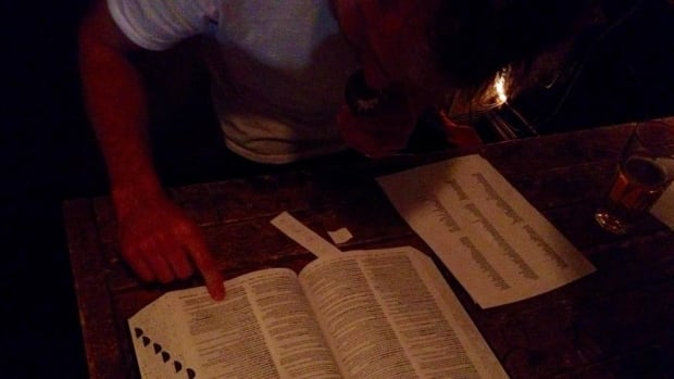 Looking up words to give contestants at the Spelling Bae, a monthly event hosted by Eli Burnstein at The Ossington.