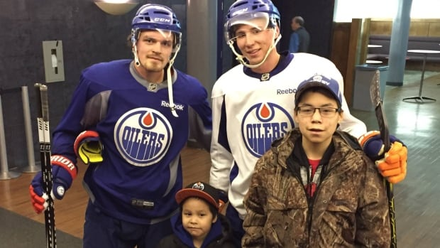2015 Shoot for Success winners Nolan Norberg (left) and Chad Eetoolook pose with Edmonton Oilers Anton Lander (in blue) and Tyler Pitlick (in white) during their trip last year. The program, started by Colin Goyman, aims to incentivize attendance in school by giving a chance for students who attend regularly to win a trip to an NHL game.