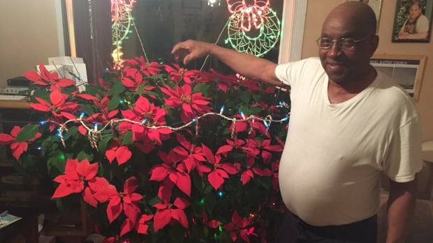 Frankie Allison regularly waters and fertilizes his 19 year old poinsettia