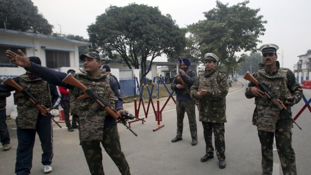 Security personnel stand guard inside the Indian air force base at Pathankot on Monday, Jan. 4, 2016. The country's defence minister said Tuesday the last of six gunmen who attacked the sprawling base over the weekend had been killed.