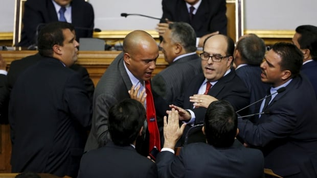 Hector Rodriguez, centre,, deputy of Venezuela's United Socialist Party (PSUV) argues with Julio Borges, second from right, and others deputies of the Venezuelan coalition of opposition parties Tuesday in Caracas.