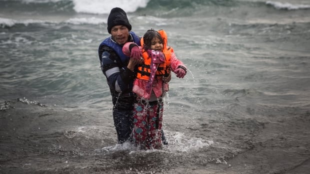 A man carries a child as they try to reach a shore after falling into the sea while disembarking from a dinghy on which they crossed a part of the Aegean sea with other migrants, from Turkey to the Greek island of Lesbos, on Sunday, Jan. 3, 2016.