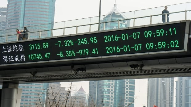 People walk in the Lujiazui Financial Zone in Shanghai on Thursday across a pedestrian bridge with an electronic display showing figures for the Shanghai, top, and Shenzhen, bottom, stock exchanges.