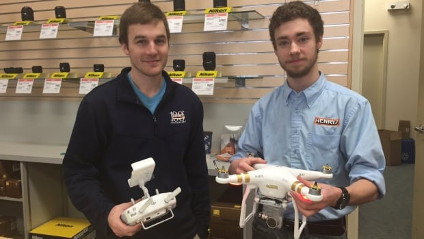 Sales associates at Henry's Camera Store in Sudbury, Tom Spencer (left) and Jackson Picard, are showing off a popular drone model.