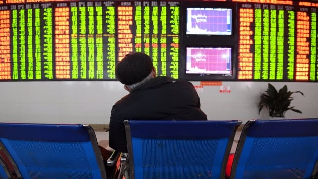 An investor sits in front of a screen showing stock market movements in China's Anhui province on Monday. The country's 'circuit breaker' intervened to curb market volatility, stopping all trading Monday, and again Thursday, before China suspended the move.