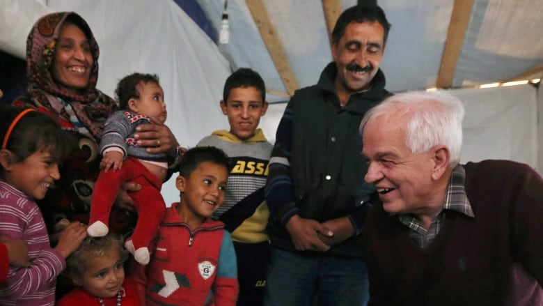 Immigration Minister John McCallum, right, speaks with a Syrian family  inside their tent, during his visit to a refugee camp in the southern town  of ...