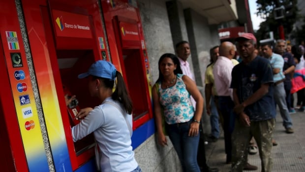 Venezuelans line up to withdraw cash from an automated banking machine. As emerging markets start to become unstable, currency controls may be returning to fashion.