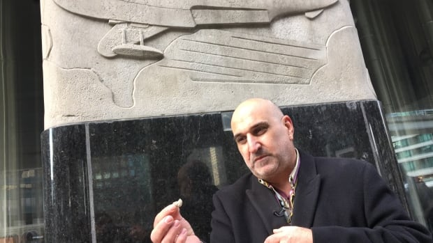Sculptor Louis Temporale Junior shows CBC News a chunk of stone that has fallen off a bas relief carved by his father on what is now the Air Canada Centre