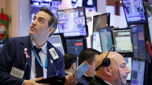 Gregory Rowe, left, with Livermore Trading Group, keeps an eye on stock prices at the New York Stock Exchange on Friday. The Dow Jones industrial average lost 6 per cent on the week, or just over 1,000 points, its worst start to a new year ever.