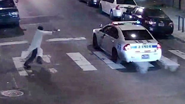 A still image from surveillance video shows a gunman approaching a Philadelphia Police vehicle in which Officer Jesse Hartnett was shot late Thursday night.