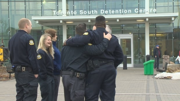 Correctional officer, Al Riley, right, celebrates with his colleagues at the Toronto South Detention Centre, after reaching a deal with the province.