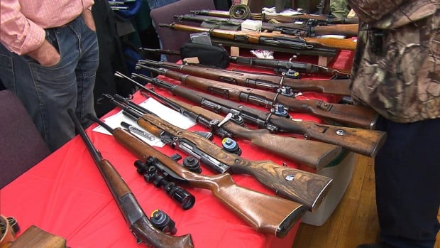 An exhibitor displays his rifles at a gun show in Longueuil on Jan. 9, 2016.