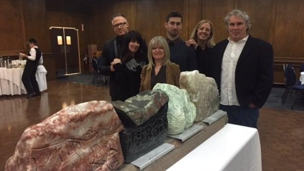 Bonnie Bricker, centre, with family and friends of Reid Bricker, gather around the 33-year-old's sculptures at Winnipeg's Shaarey Zedek Synagogue on Sunday.