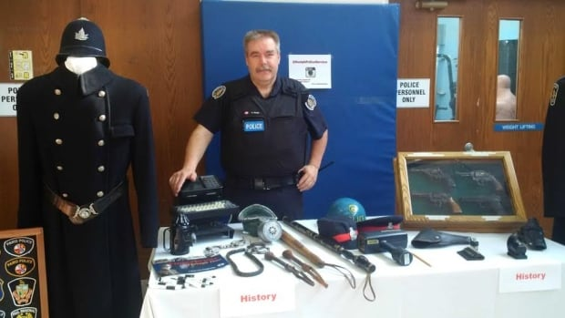 Guelph police school liaison officer Attila Korga displays artifacts from the force's history.