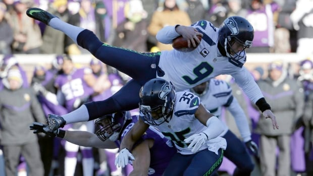 Seattle Seahawks punter Jon Ryan (9) jumps over Minnesota Vikings linebacker Casey Matthews (59) as he runs the ball during the first half of an NFL wild-card football game against the Minnesota Vikings, Sunday, Jan. 10, 2016, in Minneapolis.
