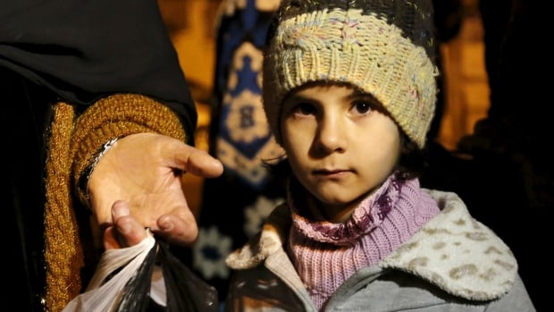 A Syrian girl waits with her family as they depart after an aid convoy entered Madaya, Syria, on Jan. 11, 2016, the day the convoy went into the besieged town where thousands have been trapped without supplies for months and people are reported to have died of starvation.