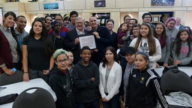 Former MP and University of Winnipeg president Lloyd Axworthy is joined by Point Douglas NDP MLA Kevin Chief and dozens of young people at an event honouring Axworthy at the Manitoba Indigenous Cultural Education Centre on Tuesday.