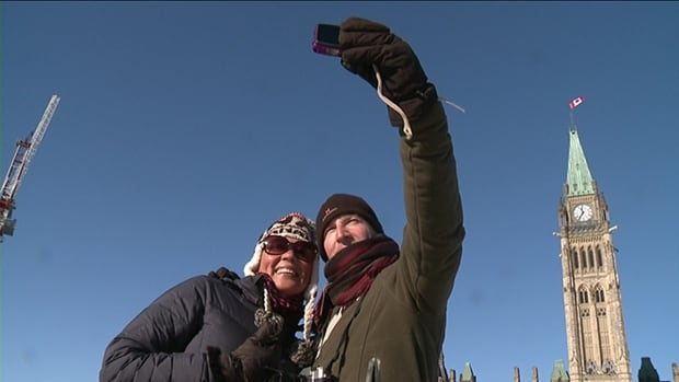 Tourists take a selfie on Parliament Hill in Ottawa on Jan. 13, 2016. The building will be covered up in scaffolding in 2018 as major repair work is carried out.