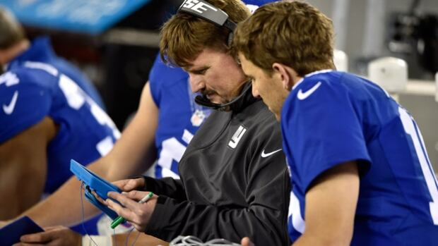 Ben McAdoo, centre, shown going over plays with Giants' quarterback Eli Manning, is moving up from his offensive coordinator role to head coach, succeeding Tom Coughlin, according to a report.