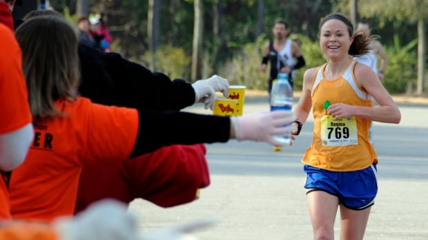 Women's winner, Regina Horak, of Madison Wis., smiles as she reaches for water near the 18 mile marker during the annual Bi Lo Myrtle Beach Marathon, in February 2013.