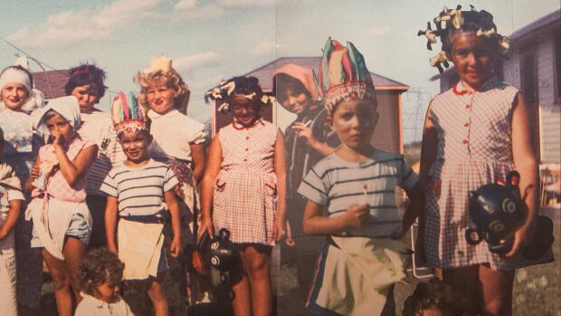 One of the displays in a Kelowna exhibition on privilege and racism features two enlarged images of Fern Helfland as a nine-year-old in Toronto. In these pictures, taken at a costume party, Helfland is wearing blackface and her brother is wearing a First Nations headdress.