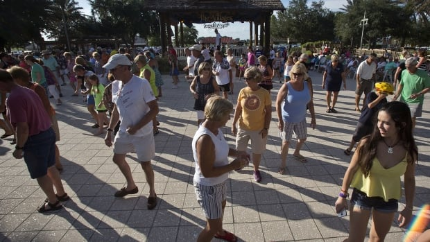 People dance at sunset in The Villages retirement community in Central Florida. While some financial planners say you'll need more than you imagine to retire, others suggest you need less.