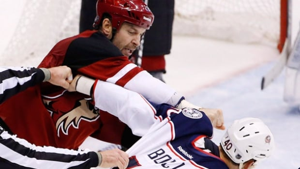 Former Arizona Coyotes enforcer and all-star captain John Scott, left, punches Columbus Blue Jackets forward Jared Boll during a fight in the second period of an NHL game on Dec. 17, 2015, in Glendale, Ariz.