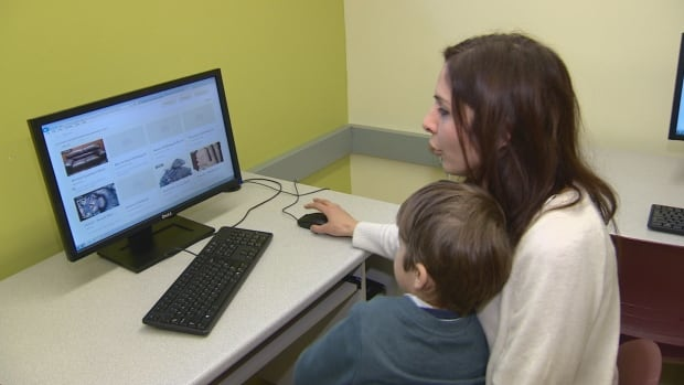 A new Canadian explores the first postings on the HOME website with her son at WoodGreen Community Services on the Danforth.
