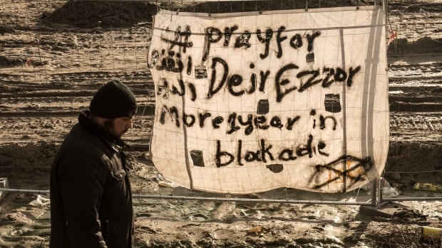 A man walks past a banner reading 'Pray for Deir Ezzor' at a migrant camp in Calais, France last month. Deir Ezzor is also known as Deir al-Zour, one of the regions where ISIS and Syrian government forces are battling for control.