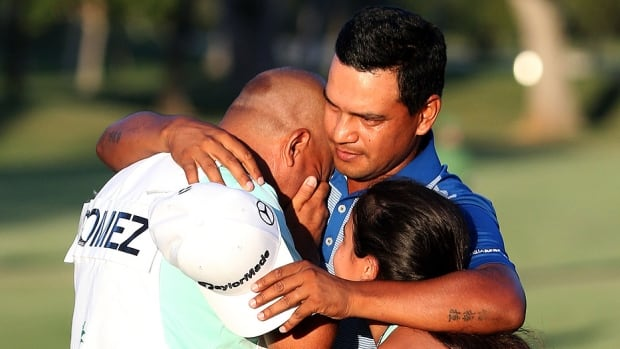 Fabian Gomez of Argentina celebrates with his caddie after winning during a playoff in the final round of the Sony Open at Waialae Country Club in Honolulu, Hawaii, on Sunday. The 37-year-old Argentine enjoyed a run of seven straight birdies and won with his 11th birdie of the day on the second playoff hole to outlast Brandt Snedeker. Graham DeLaet was the top Canadian, finishing six shots back.