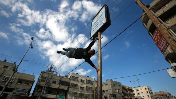 The sport of parkour, also known as free running, is popular with a group of young men in Gaza who have been using the war-torn city as a training ground due to lack of suitable indoor space. Here a man demonstrates a 'flagpole' manoeuvre on Jan. 15, 2016.