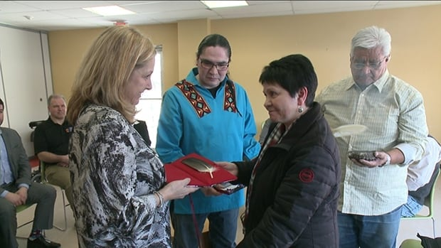 Jan Crozier, supervisor of operations at the Ottawa courthouse, receives an eagle feather from Algonquin elder Claudette Commanda.