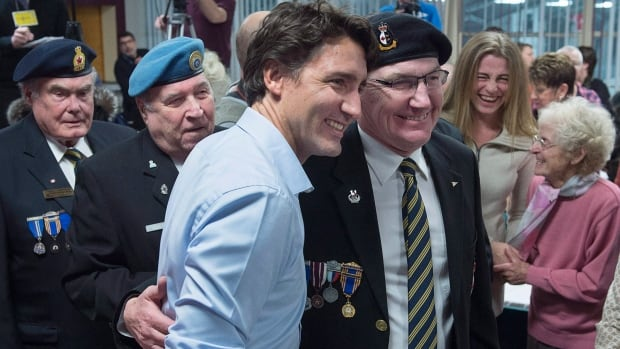 Prime Minister Justin Trudeau poses with veterans at the spaghetti dinner in St. Andrews, N.B. The federal Liberal cabinet is meeting in the seaside town, working on their plans for the year, including the upcoming budget.