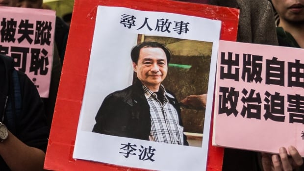 In this picture taken on January 3, 2016, a protester holds up a missing person notice for Lee Bo, 65, one of five Hong Kong booksellers from the same Mighty Current publishing house who have gone missing.
