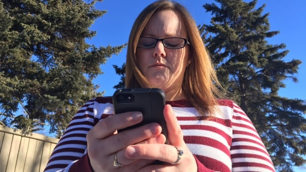 Bobbi Michaud views pictures of bills sent by Direct Energy to her landlord, which say she has an outstanding balance even though she hasn't lived in Grande Prairie since 2010. She says she never even opened an account with the gas provider.