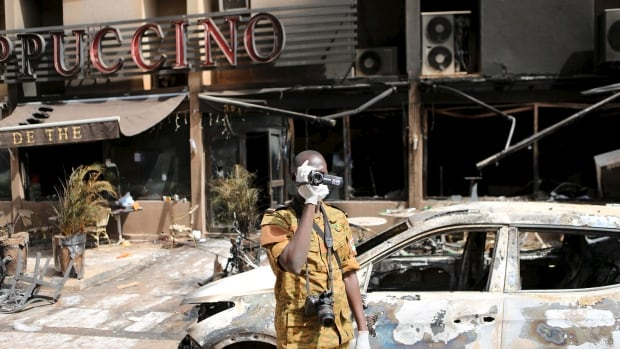 A soldier films in front of the burned-out exterior of the Cappuccino restaurant in Ouagadougou, Burkina Faso, after security forces retook the Splendid Hotel from Al-Qaeda fighters.