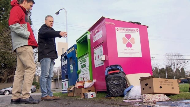 Charles Stratford shows CBC reporter Jesse Johnston the piles of junk that pile up at a row of charity donation bins near his home in Richmond, B.C.