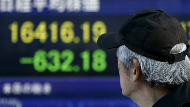 An electronic board shows Japan's Nikkei average outside a brokerage in Tokyo on Wednesday. Japan's benchmark stock index tumbled to a 14½ month low as global markets were battered by plunging crude prices that slid below $27 US a barrel.