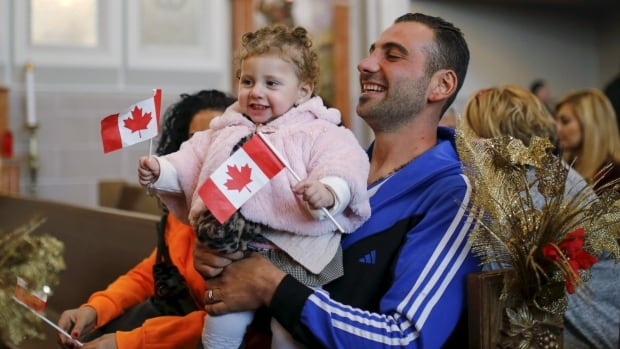 Syrian refugee Kevork Jamgochian holds his daughter Madlin at the St. Mary Armenian Apostolic Church during a welcome serivice at the Armenian Community Centre of Toronto in January 2016. About 7,000 Syrian refugees have already settled in Ontario since Dec. 10.