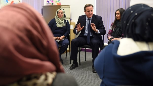 British Prime Minister David Cameron speaks with women attending an English-language class. Some migrants to Britain who cannot pass an English test within two and a half years of arriving may not be allowed to stay, Cameron said in a move aimed at fostering greater integration of Muslim women.
