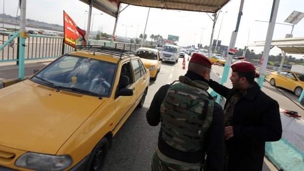 Iraqi security forces man a checkpoint on the main road from Baghdad's central Jaderiyah district to Dora on the southern outskirts of the Iraqi capita on Jan. 18, as authorities search for three missing Americans.