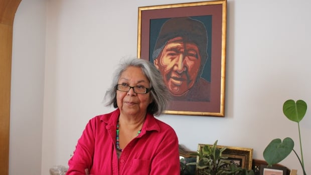 Patricia Ningewance stands with a painting she did of her grandma, who was the inspiration behind her book, Talking Gookum's Language.