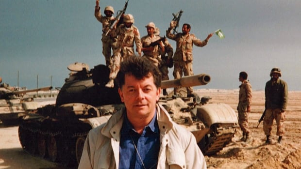 A younger Brian Stewart, in the desert outside Kuwait City, reporting for CBC News in 1991.