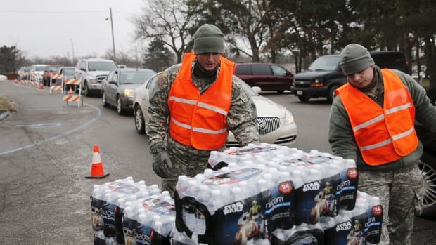 Michigan National Guard members help to distribute water to a line of residents in their cars in Flint, Michigan on Jan. 21, 2016.