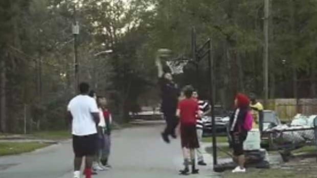 An officer of the Gainesville Police Department identified as Bobby White dunks while playing basketball in the street after responding to a noise complaint about a group of friends playing the street. The officer decided not to ticket anyone.